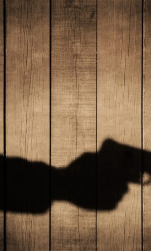 Outstretched arm with a gun. Black shadow on natural wooden background, with space for text or image.